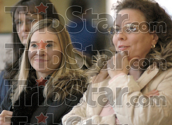 Smiles: Indiana State University staff members Karen Mandino and Dawn Underwood smile as they watch the swearing-in ceremony in the food court of campus Tuesday afternoon.