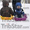 Two-year-old Sam Truxal, right, admires the view as he is pulled, along with sister, Bailey, 5, up the sledding hill at Deming Park Tuesday by dad, Troy Truxal.