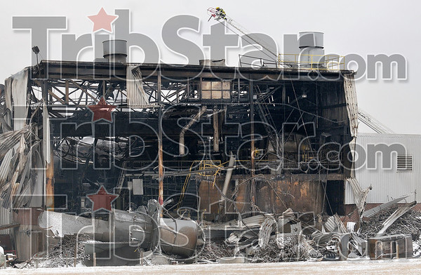Tribune-Star/Joseph C. Garza<br /> Fighting from the sky: Terre Haute Fire Department Lt. Joe Swan extinguishes the smoldering remains of Monday night's fire at the former International Paper complex Tuesday.