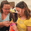 Tribune-Star/Joseph C. Garza<br /> Susan Brown, 14, and Madison King, 12, work together to build a holder for King's cellphone Thursday during the Express Yourself! program at the Vigo County Public Library.