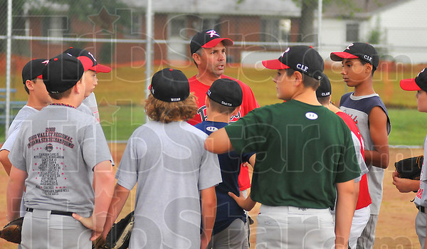 Leader: Mark Clinkenbeard talks with his team of 12 year-old Cal Ripken players before practice Wednesday evening.