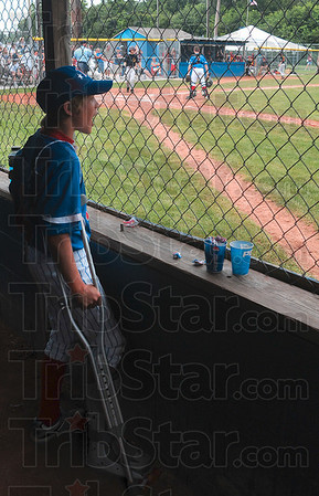 Tribune-Star/Joseph C. Garza<br /> A loud dugout: Terre Haute North Little League's Damon Prifogle doesn't let a leg injury stop him from cheering on his teammates during the team's semifinal game against McCutcheon Thursday at the Terre Haute North Little League Ballpark. The cheering worked; the team won 13-6.