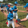 Tribune-Star/Joseph C. Garza<br /> Way to go, kid!: Terre Haute North Little League coach Mike Schlosser congratulates Jonathan Eilbracht on his score during the team's semifinal win over McCutcheon Thursday at the Terre Haute North Little League Ballpark.