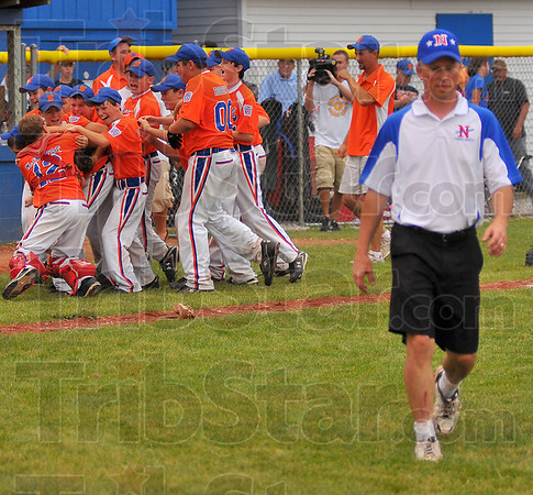 Done too soon: Terre Haute North manager Hans Eilbracht walk back to his team as the Bartholomew County team celebrates their State Championship in the background.