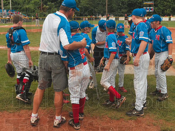Tribune-Star/Joseph C. Garza<br /> Nice inning, kid: Terre Haute North Little League coach Mike Schlosser offers a hug to Zach Haase after Haase had a good inning during the team's semifinal game against McCutcheon Thursday at the Terre Haute North Little League Ballpark.