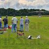 Three point landing: Bob Bedwell brings his light sport aircraft into Terry Brentlingers' grass airstrip while a group of Radio Control piliots watch.