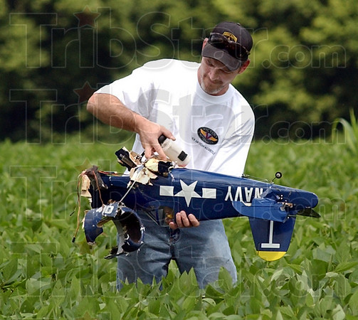 Breaks of the game: Radio Control pilot Ed Brazzell picks up the pieces of his Corsair from a nearby bean field. His plane was in a mid-air collision with a scale model of a Japanese Zero.