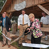 Tribune-Star/Joseph C. Garza<br /> For his dedicated service: Sharon Miles, the wife of the late city councilman, Chuck Miles, cuts a ribbon as city councilman John Mullican, Mayor Duke Bennett and Turk Roman, look on Friday at the shelter dedicated to Chuck Miles at Washington Park.