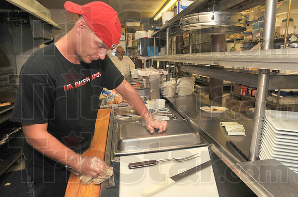 Above minimum: Luke Renick works in the kitchen of George Azars' Saratoga restaraunt. Since all of Azars' employees already earn above the minimum wage, he doesn't see any effect of the new national minimum standard.