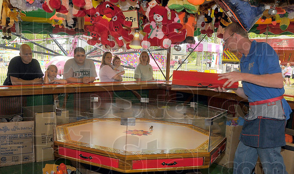 """Run and hide: Joe Kuta sets the mouse free in """"The Mouse Game"""". It is one of the midway games at the Brazil Rotary Club Fourth of July Celebration at Forest Park."""