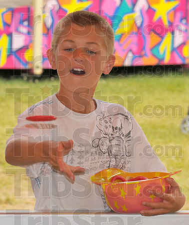 Ringer: Drake Beauchamp tries to ring a bottle at one of the many game booths at the Brazil Rotary Club Fourth of July Celebration.