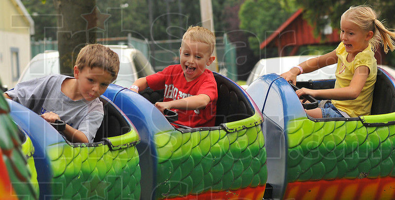 Whatta ride: Logan Rambo, Tyler Patton and Morgan Trivett ride the dragon roller coaster at the Brazil Rotary Club Fourth of July Celebration Friday afternoon. The festival continues through today, ending with fireworks at dark.