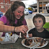 Family time: Anna Moore helps her brother Moses Hamm finish his barbequed ribs at the  Clabber Girl Brickyad BBQ. Saturday afternoon.
