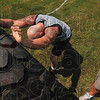 Tribune-Star/Joseph C. Garza<br /> One more heave ho!: Chris Porter gathers his strength to push a large farm tractor tire end over end one more time as John Barrett, right, encourages his Saturday during the Gladiator Challenge at Dever Distributing.