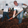 Tribune-Star/Joseph C. Garza<br /> Unison Engine Components employee Kelly Zbiegien shovels mulch onto a flatbed truck along with several other co-workers Saturday at Deming Elementary School.