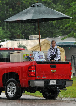 Dry ice cream: Kiersten Snapp shelters under and umbrella in the back of a truck as she makes the rounds of Sullivan County Park and Lake Saturday afternoon.