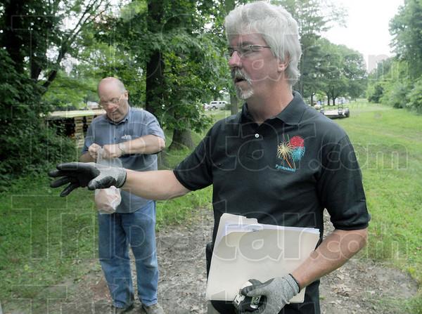 Safety first: Pyrotechnist Jim Stanfill (R) talks with members of his firing crew about safety on the job during preparations for the annual Fourth of July fireworks display in Terre Haute. Aerial Arts Fireworks owner Mark Adamson handles an eight inch shell.