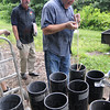 Mortar: Pyrotechnist Jim Stanfill (L) watches as Mark Adamson demonstrates loading an eight inch shell into a mortar rack as they prepare for several shoots during the Fourth of July celebration.