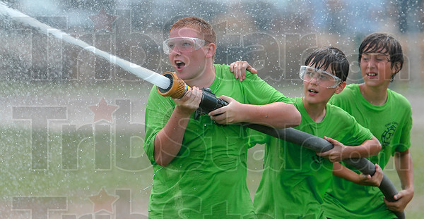 Tribune-Star/Joseph C. Garza<br /> Stream team: Green team members Tony Eley, Wyatt Johnston and Logen McGrew command the hose and nozzle as they play a game of water ball against fellow participants in the Vigo County Junior Fire Camp Wednesday at the Wabash Valley Fairgrounds.