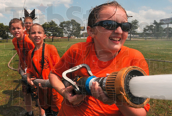 Team effort: There was no shortage of encouragement for Jaydon Tichenor, 11, from her orange team teammates as she directed the nozzle in a game of water ball Wednesday during the Vigo County Junior Fire Camp at the Wabash Valley Fairgrounds.