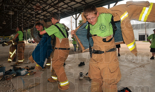 Now we don our fire apparel: Eleven-year-old AJ Lalen, right, hurriedly puts on firefighter turnout gear during a race against his fellow Vigo County Junior Fire Camp participants Wednesday at the Wabash Valley Fairgrounds.