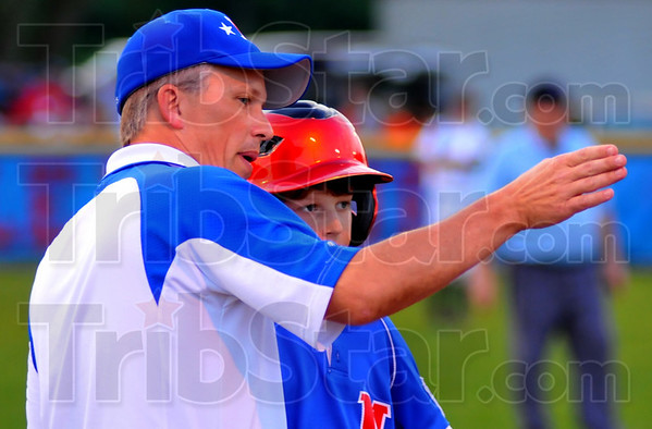 Go home: Terre Haute North coach Hans Eilbracht talks with baserunner Zach Edwards about the upcoming play. Edwards scored on a close play at the plate.