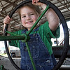 Oh Deere: Three-year-old Elizabeth Boling takes the wheel of a John Deere tractor at the Vigo Co. 4-H Fair Monday morning. She's even color coordinated, wearing her green shirt to match the John Deere brand colors.