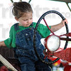 Nothin' to it: Three-year-old Elizabeth Boling takes the wheel of her grandfather's antique Farmall tractor at the Vigo Co. Fairgrounds Monday morning.