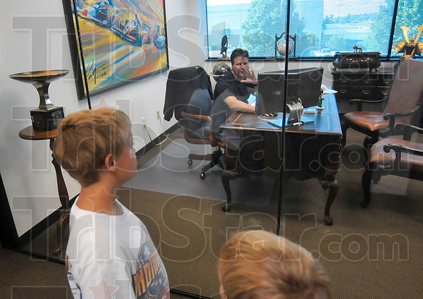Tribune-Star/Joseph C. Garza<br /> Hello from racing royalty: Michael Andretti, co-owner of Andretti Green Racing, waves to West Terre Haute residents Christopher and Creed Fritz as they tour the racing team's headquarters Monday in Indianapolis.