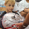 Tribune-Star/Joseph C. Garza<br /> Marco's helmet: Creed Fritz, 8, holds a helmet used by Marco Andretti as he and his brother, Christopher, tour the Andretti Green Racing headquarters Monday in Indianapolis.