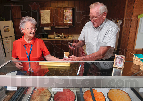 Tribune-Star/Joseph C. Garza<br /> Ice cream team: Wanda Smith hands her husband, Bill Smith, an ice cream cone for a customer's order Tuesday at Grandma & Grandpa's Ice Cream Shop on US 41.