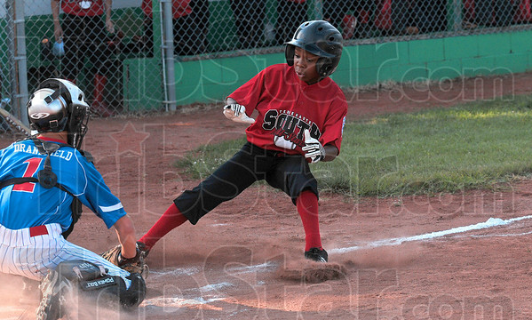 Tribune-Star/Joseph C. Garza<br /> Uh oh: Terre Haute South's A.J. Smith tries to stop in his tracks as he realizes he couldn't beat the throw to homeplate while North Terre Haute catcher Lane Dransfield waits for him with the tag Tuesday at the West Terre Haute Little League fields.