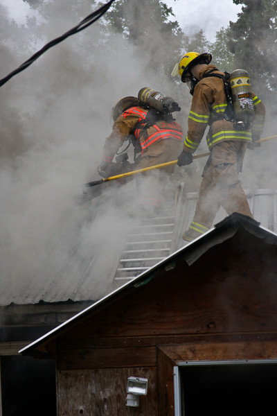 John Beebe makes the first cut ventilating the roof with Tim Gonyea helping.