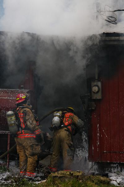 Central Mat-Su firefighters Tawnya Hightower and Greg Adamietz hit a hotspot in a wall.