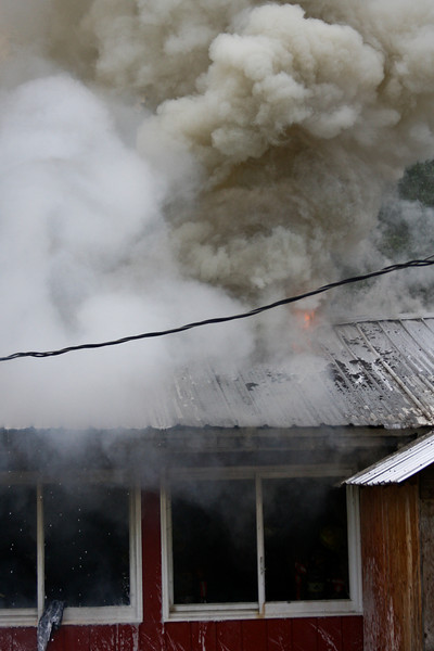 Crews work interior fire attack with superheated gasses escaping from the roof overhead.
