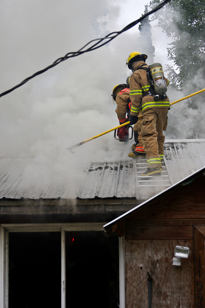 Tim Gonyea and John Beebe perform roof ventilation with crews working fire attack inside.