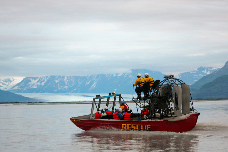The Water Rescue Team's airboat blazes in front of the Knik Glacier, making a turn back downstream.