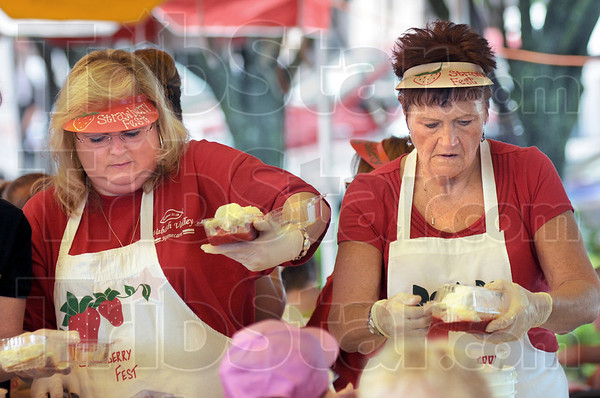 Service line: Becky Gwizdala and Marilyn Locke prepare strawberries and ice cream for patrons attending the annual downtown Strawberry Festival.