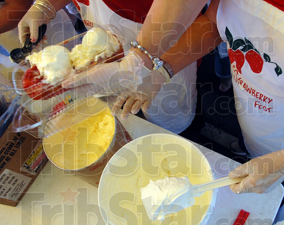 Production: Becky Gwizdala and Marily Locke prepare strawberries and ice cream for patrons of the annual Strawberry Festival Thursday afternoon in downtown Terre Haute.