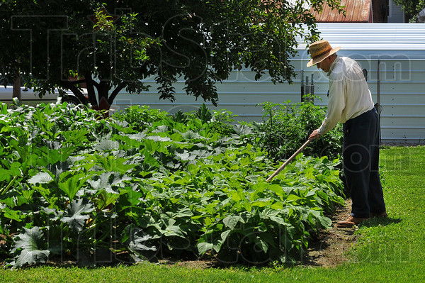 A little off the side: John Greenwalt tends to grass and weeds in his garden.