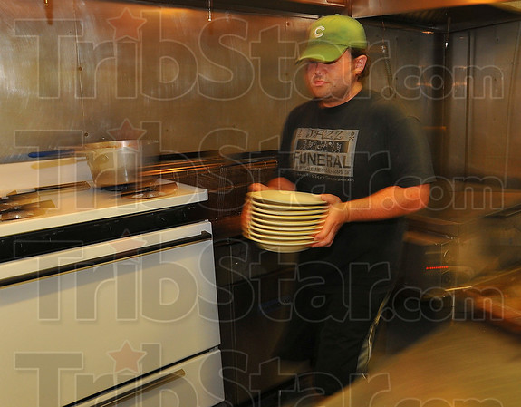 Stocking up: Jason Neibrugge stocks new plates on the shelves of the kitchen of JDs Steakhouse Thursday afternoon.