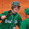 Home run happy: West Vigo's Cody Thornton celebrates a teammate's homerun with the third base coach during the Vikings' 11-6 semistate win Saturday at Avon High School.