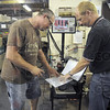 At work: Director of operations Dean Decker (R) talks with machine operator Tom Hudak during the workshift Thursday afternoon. The company makes auto transmission parts for a major auto maker.