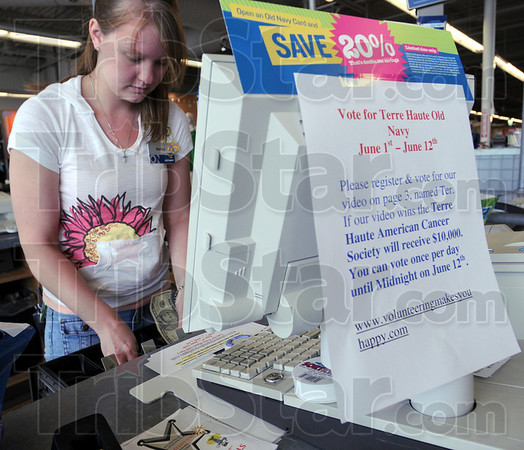 Vote: Old Navy employee Mallory Speth makes change for a customer Thursday afternoon as a sign attached to the register asks for votes for the store video attempting to win $10,000 cor the Cancer Society.