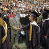 Congratulations: Terre Haute North head basketball coach Todd Wolfele shakes hands with graduating class members as they walk the Processional during Sunday's graduation activies at Hulman Center.