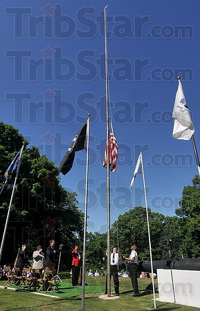 Tribune-Star/Joseph C. Garza<br /> Raising Old Glory: VFW Post 972 Chaplain Don Smock and member Dan Martin raise the flag during a Memorial Day ceremony Sunday at Highland Lawn Cemetery.