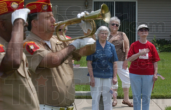 Tribune-Star/Joseph C. Garza<br /> Flag Day salute: Anthony Square residents Wanda Wildin, Mary Baker and Rosemarie Taylor stand at attention as Henry Shattuck of the Marine Corps League plays the trumpet Sunday at the senior citizen home. At left is fellow Marine Corps League member Dan Martin.