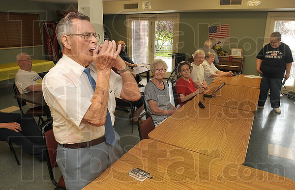 "Tribune-Star/Joseph C. Garza<br /> For Old Glory: Anthony Square resident Wilbur Moore plays ""You're a Grand Old Flag"" on his harmonica as he and his fellow residents celebrate Flag Day Sunday at the senior citizens home."