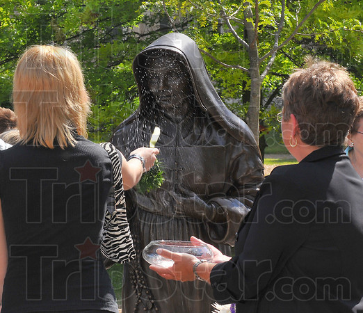 Blessed: Holy water cast by pine branches is used to bless the bronze statue of St. Mother Theodore Guerin Sunday morning.