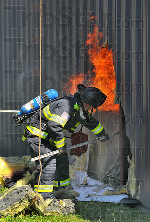 Hot afternoon: Terre Haute City firefighter Jimmy Holbert uses a pike pole to pull interior walls apart at the Family Dollar store on Poplar street Sunday afternoon. Fighting the fire from the rear of the building, the hole was made to allow water to stream into the heart of the fire.